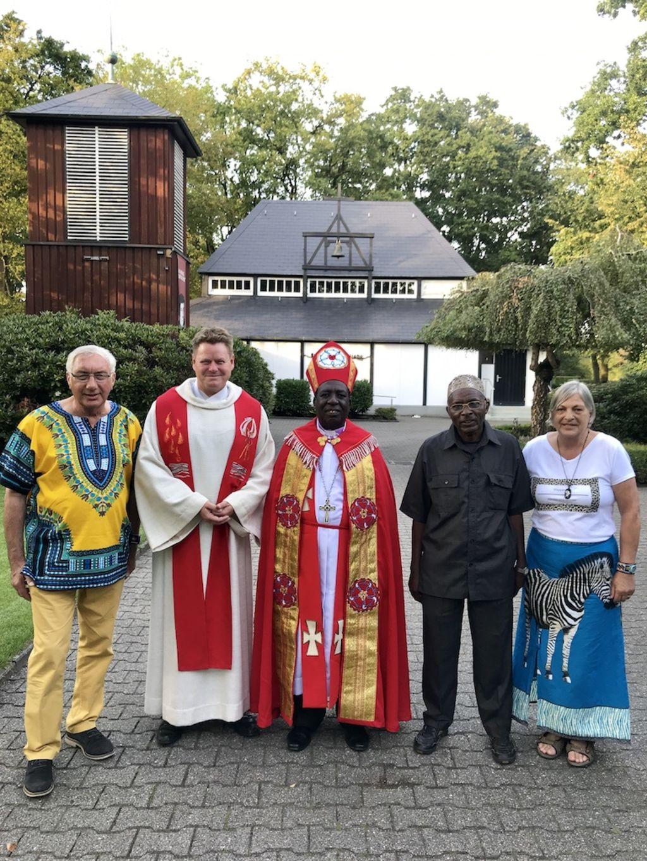 Jacoba und Walter Schulz (außen) zusammen mit dem lutherischen Bischof Amon Kinyunyu und dem muslimischen Bürgermeister Mohamed Mayingu sowie Pastor Thorsten Jacobs 2019 vor der Pauluskirche in Dalum.
